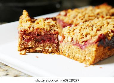 Peanut Butter and Strawberry Jelly Oat Bar Squares on a White Plate