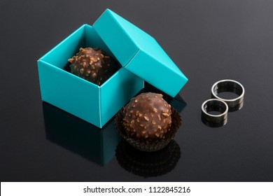 Peanut and chocolate pralines in an open blue box next to a pair of wedding rings on a reflexive black background
