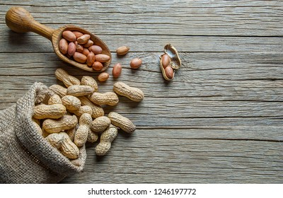 Peanut in nutshell in burlap sack or sackcloth with wooden shovel. Composition of peanuts serving to make oil, peanut butter. Great for healthy and dietary nutrition. Concept of condiments