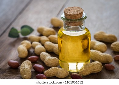 Peanut oil in glass bottle and peanuts on wooden table