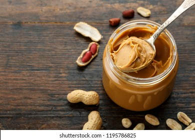 peanut paste in an open jar and peanuts in the peel scattered on the table