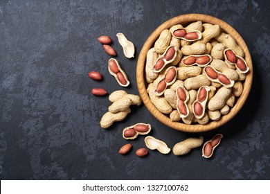Peanut in wooden bowl on black background with copy space.Top view. Wooden plate with peanut on black background. Space for text