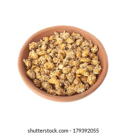Peanuts candied in honey with sesame in bowl of clay  isolated over white