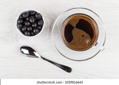 Peanuts in cocoa powder, black coffee in cup and spoon on wooden table. Top view
