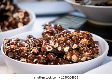 Peanuts and hazelnuts in a brittle made of toffee broken into sparate pieces in a bowl for sale at a local market