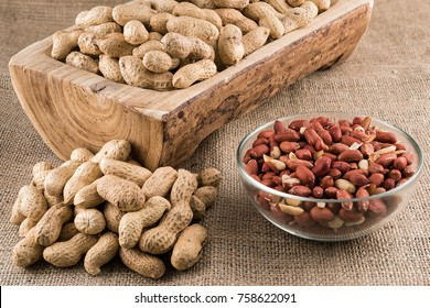Peanuts in nutshell on a piece of wood and peeled peanuts in a bowl on sackcloth