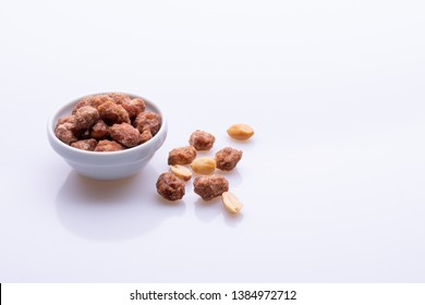 Peanuts praline sweet in a white bowl, on white background, angle view, soft light, copy space