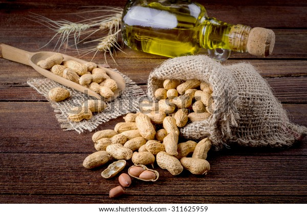 Peanuts in sack and spoon on dark wooden background