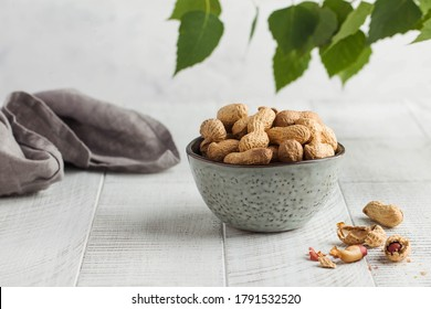 Peanuts in a shell in a gray bowl on a white wooden background with green leaves. Healthy snacks. Copy space.