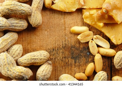 Peanuts in the shell and out laying on a wooden table.