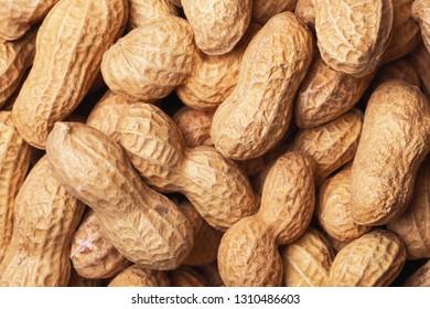 Peanuts in shells closeup pile pattern background. Helathy vegetarian diet food texture.