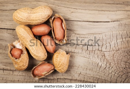 Peanuts in shells on wood background