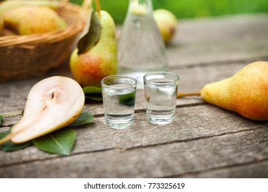 Pear alcohol drink in two shot glass with fresh pears