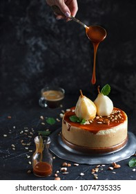 Pear chesecake with caramel and caramel drop in black background
