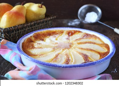Pear clafoutis and yellow pears in wicker basket, french cuisine, rustic style