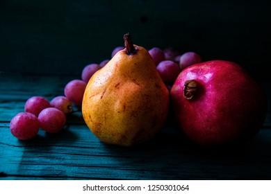 pear, pomegranate and grapes on wooden background