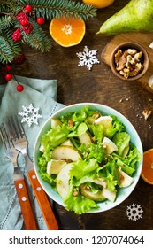 Pear Salad, Walnut, Camembert Cheese and Vinaigrette Dressing on a festive Christmas table.Traditional french cuisine. Top view flat lay background. Copy space.