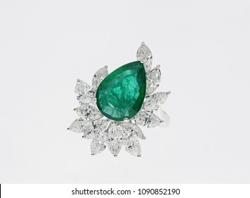 Pear Shaped emerald ring with diamond closeup on isolated white background