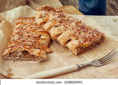 Pear strudel on a baking sheet sprinkled with sesame seeds and flax with a cup of coffee on a wooden table. Rustic style. dark style