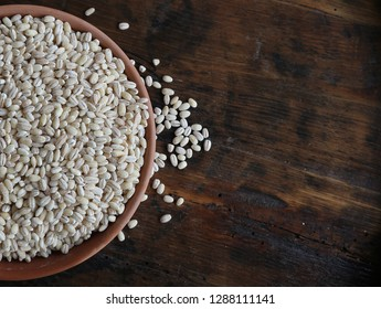 Pearl barley in a terracotta bowl on an old weathered wooden table