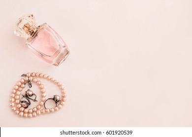 Pearl beads with jewelry earrings and a ring. A bottle of female perfume on a light background
