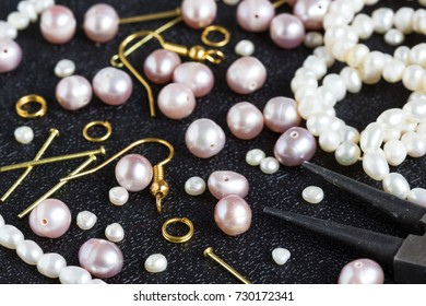 Pearl beads and tools for making jewelry on a black background.