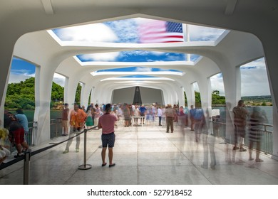 Pearl city, United States - August 21, 2016: Visitors inside the USS Arizona memorial in Pearl Harbor, Hawaii, with the United States flag at half mast.
