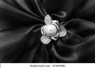 Pearl and diamonds brooch on black satin as a background