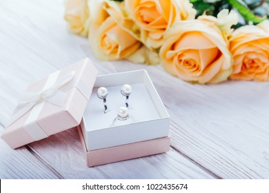 Pearl earrings in the gift box with roses