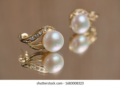 Pearl earrings on a glass table. Close up.