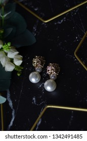 Pearl  gold earrings with lion shaped. fashion concept on black background. Top view. woman accessoires