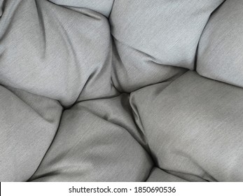 Pearl gray vintage quilted cushion texture. Cushion cover filled with cotton ideal for chill out environment. Elegant and hygge interior decoration. Fragment of light soft gray textile as background.
