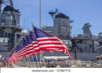 PEARL HARBOR, HAWAII - SEPTEMBER 19, 2012: A row of U.S. flags stands in front of the U.S.S. Missouri. The Japanese surrender, ending World War II, was signed on this battleship in Tokyo Bay.
