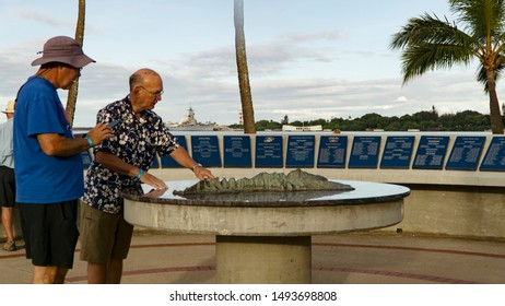 Pearl Harbor, Hawaii / USA - September 1, 2019: After a 15-month closure, the USS Arizona Memorial finally reopened today. Here, two visitors look over a diagram with the memorial in the distance.