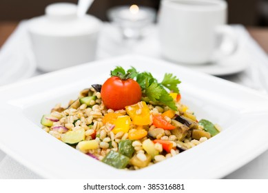 Pearl (hulled) barley cooked with vegetables arranged on square white plate, selective focus closeup