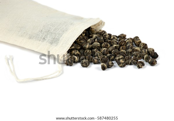 Pearl jasmine green tea spilling out of a washable Eco-friendly tea bag.