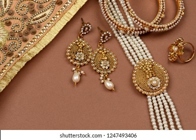 Pearl Jewelry on a brown background,Golden scarf,Pearl bracelet,pearl hair clip,pearl necklace pearl earrings,finger ring.fashion and design of jewelry. Indian traditional jewellery,jewelry background