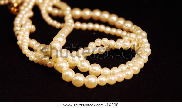 A pearl necklace with 3 strands laying on black velvet