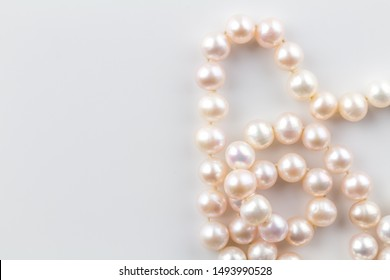 Pearl necklace background with a string of pink pearls isolated on white background - top view photograph