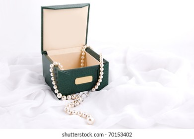Pearl necklace in box over white fabric