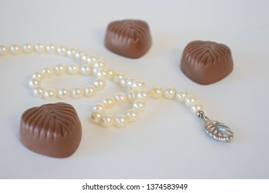 Pearl necklace and chocolate candies