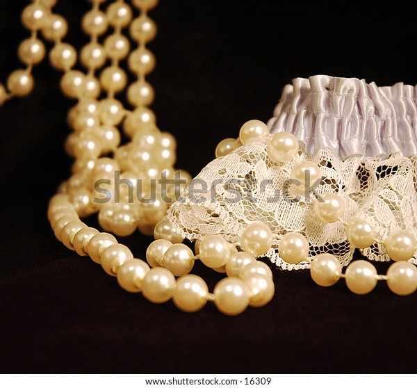 A pearl necklace draped with a lace garter on black velvet
