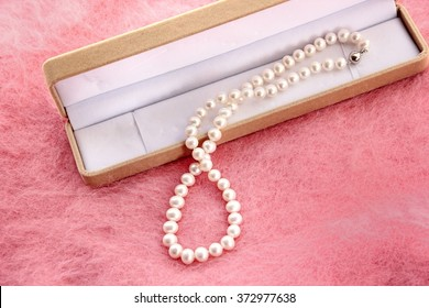 Pearl necklace with jewel box on pink background.