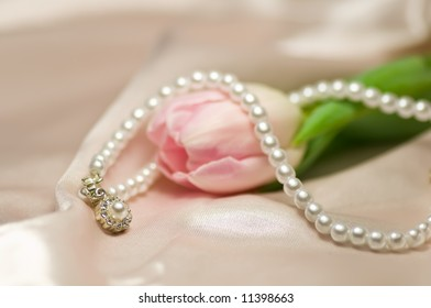 Pearl necklace on pink tulip on shiny pink silk