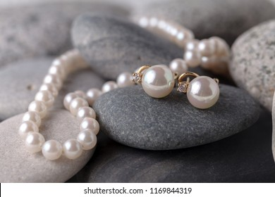 Pearl necklaces and earrings lay on green stones