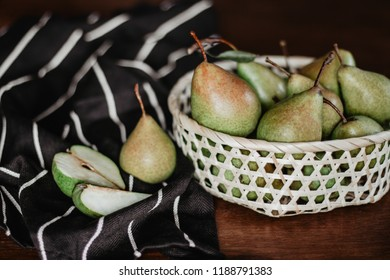 Pears in a basket on the wooden table.