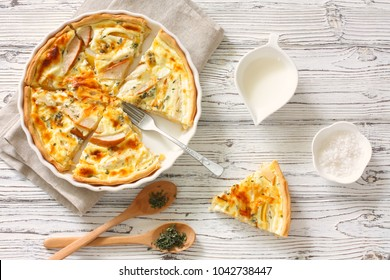 Pears and cheese pie (quiche) , bowl of cream, wood spoona, fork and salt. Top view