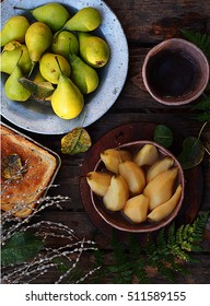 pears cooked in wine and fresh pears on a wooden table autumn