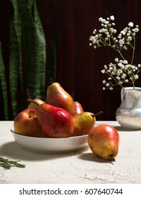 Pears and flowers on rustic table