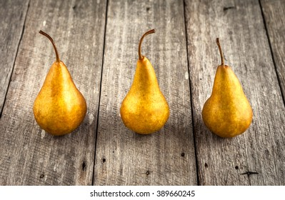 Pears with golden appearance on rustic wooden background